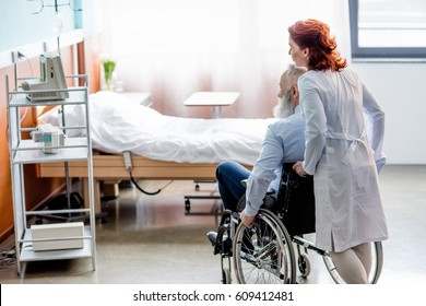 Female doctor pushing senior patient in wheelchair at hospital room