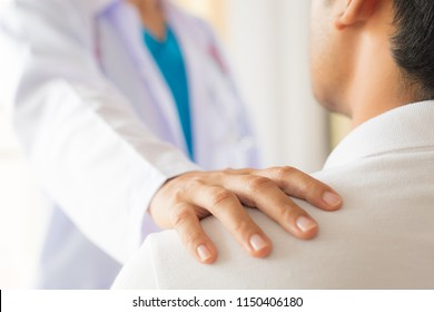 Female doctor put hand on patient shoulder for encouragement and discussion. Medicine and health care concept. Doctor and patient.