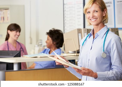 Female Doctor Reading Patient Notes At Nurses Station