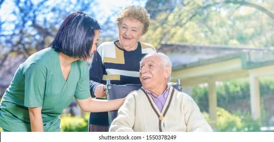Female doctor reassuring elderly retired people in the hospital garden.