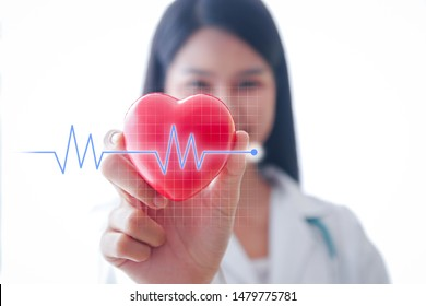 A female doctor with a red heart shaped ball There is a graphical representation of the ECG. Health care concept
