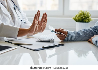 A female doctor refuses a bribe from her patient