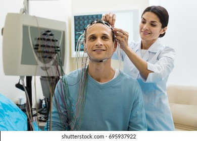 Female doctor removing electrodes from patients head