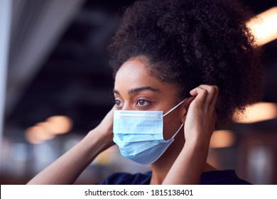 Female Doctor In Scrubs Putting On Face Mask Under Pressure In Busy Hospital During Health Pandemic