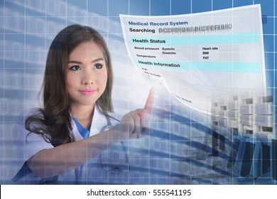Female doctor searching patient information from electronic medical record system.