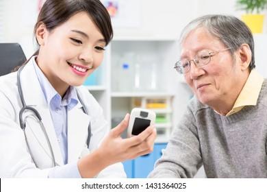 Female doctor show blood sugar test result to elder patient