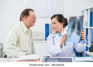 Female doctor showing to senior man results of exam
