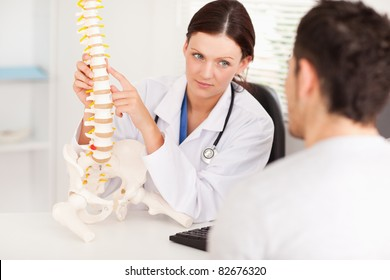 A female doctor is showing a doctor a spine
