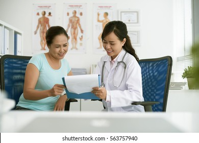 Female doctor showing test results to patient