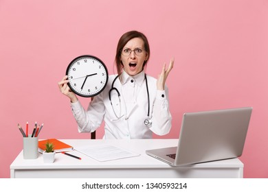 Female doctor sit at desk work on computer with medical document hold clock in hospital isolated on pastel pink wall background. Woman in medical gown glasses stethoscope. Healthcare medicine concept