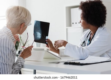 A female doctor sits at her desk and talks to a female patient while looking at her mammogram. Brest cancer prevention