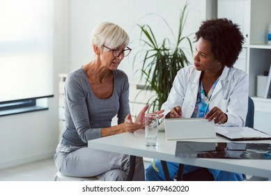 A female doctor sits at her desk and chats to an elderly female patient while looking at her  test results