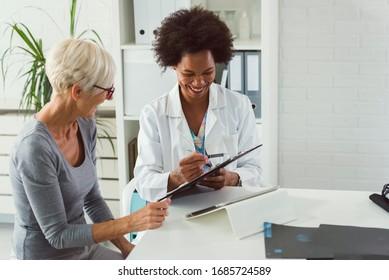 Eine Ärztin sitzt an ihrem Schreibtisch und unterhält sich bei einer älteren weiblichen Patientin, während sie ihre Testergebnisse betrachtet