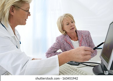 female doctor sitting at her desk pointing to a computer screen explaining something to a senior woman patient
