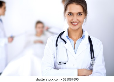 Female doctor smiling on the background with patient in the bed