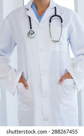 Female doctor standing with hands in pocket in medical office
