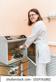 Female doctor sterilizing medical instruments