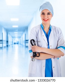 Female Doctor with Stethoscope in Hand in the Hallway of the Clinic