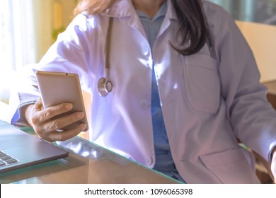 Female doctor with stethoscope hand  using mobile smart phone , sitting in relax position in free time  at medical room.