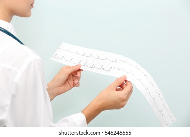 Female doctor with stethoscope holding an electrocardiogram on light background