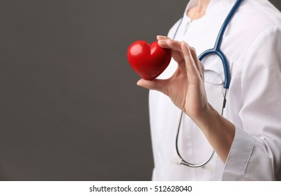 Female doctor with stethoscope holding heart, on dark background