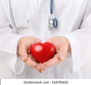 Female doctor with stethoscope holding heart, closeup