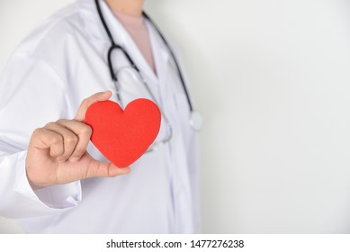 Female doctor with stethoscope holding red heart in her hand on white background. Medical and health conditions concept.