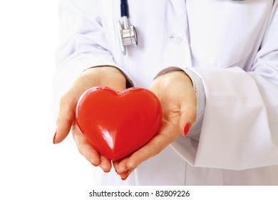 Female doctor with stethoscope holding symbol of heart on the stretched palms.