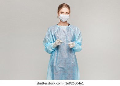 Female doctor or surgeon in medical uniform and medical protective mask holding endotracheal tube and posing on a grey background, isolated. Healthcare and emergency