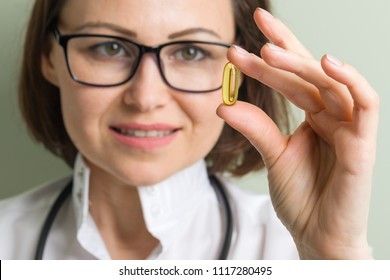 Female doctor takes vitamin capsule. Healthy lifestyle, nutritional supplements, vitamin d, e, fish oil capsules.
