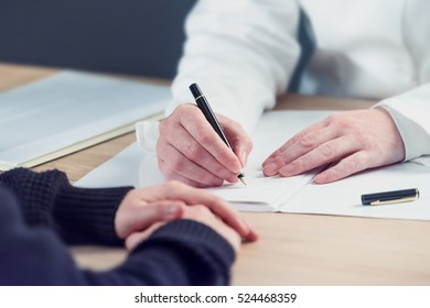 Female doctor taking notes during patient's medical exam, writing medical history record for the woman