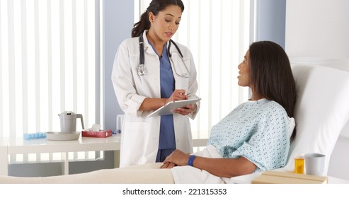 Female doctor talking to African American patient in hospital bed