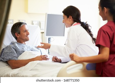 Female Doctor Talking To Male Patient In Hospital Room