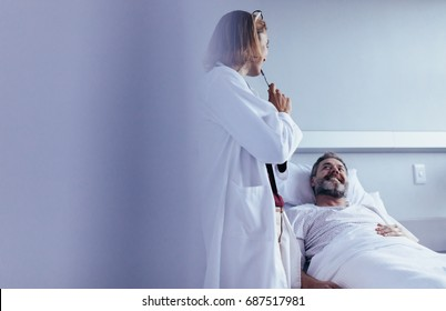 Female doctor talking to male patient lying in hospital bed. Medical professional interacting with patient in hospital ward.