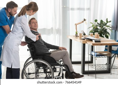 female doctor talking to mature man on wheelchair