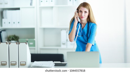 Female doctor talking on phone in diagnostic center