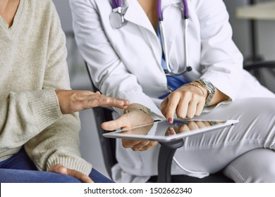 female doctor talking to a patient on a tablet