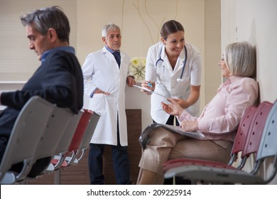 Female doctor talking to patient in waiting room.