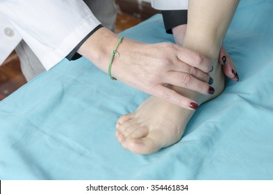 Female doctor touch the foot of patient.