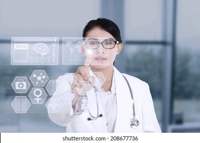 Female doctor touching medical interface on modern technology