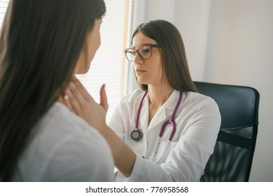Female doctor touching the throat of a patient. Young doctor palpating lymph nodes of a patient. Medical exam, healthcare, clinic, hospital examination