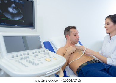 female doctor using sonogram on male patients chest