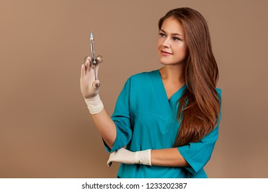Female doctor with vial and syringe in hospital. Vaccination day. beige background
