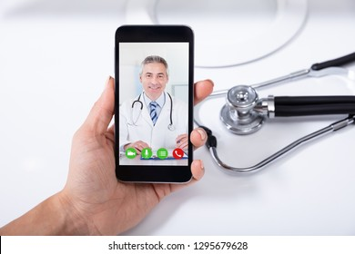 Female Doctor Video Conferencing With Happy Male Colleague On Cellphone Over Desk
