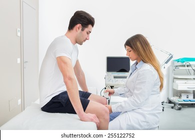 Female doctor visiting her male patient with ultrasound in medical center.