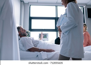 Female doctor visiting patient in hospital room. Sick man lying in bed with family sitting by and doctor.