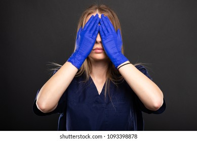 Female doctor wearing scrubs covering eyes like blind concept on black background