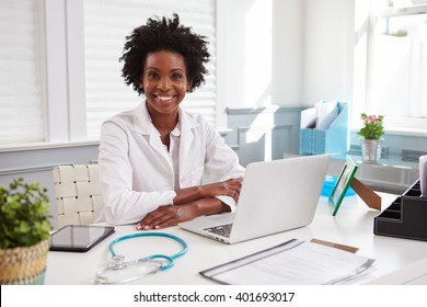Female doctor in white coat looking to camera in an office