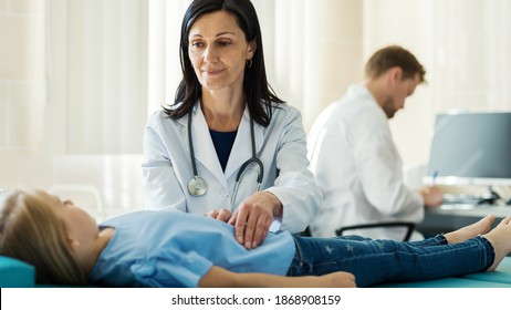 Female doctor in white coat palpating belly of girl lying on couch and talking to little patient, male doctor making notes in medical history at desk in background