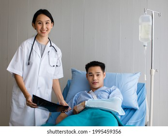 Female doctor in white dress showing X-ray film to patient man who had an arm injury that had to wear a cast. They both had smiles on their faces, indicating that the treatment was going well